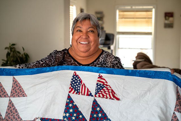 Maria Ignacia Sanchez smiles as she holds a boat quilt she made for her daughter, Maria Ureste. Photo by Alex Labry