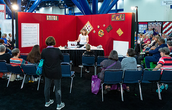 """Teresa Coates demonstrates in the """"Stitch/Sew"""" area of Open Studios at Houston Festival"""
