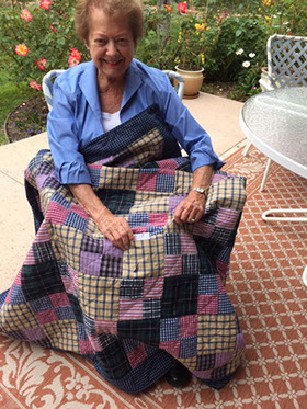 Pat Nickols with a memory quilt she made from shirts worn by her late brother as a gift for her sister-in-law. Photo courtesy of Pat Nickols.