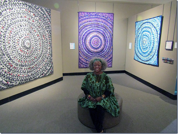 Betty Ford-Smith in front of an exhibition of several of the Pine Cone/Pine Burr quilts she made.
